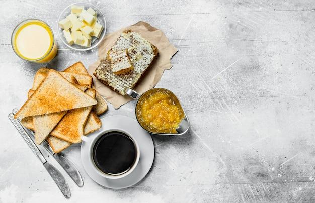 Śniadanie. chleb tostowy z masłem, miodem i konfiturą pomarańczową. na rustykalnej powierzchni.