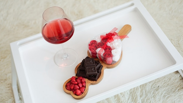 Śniadanie dla dziewczyny. walentynki rano. wino i słodycze na białej tacy. śniadanie w łóżku.