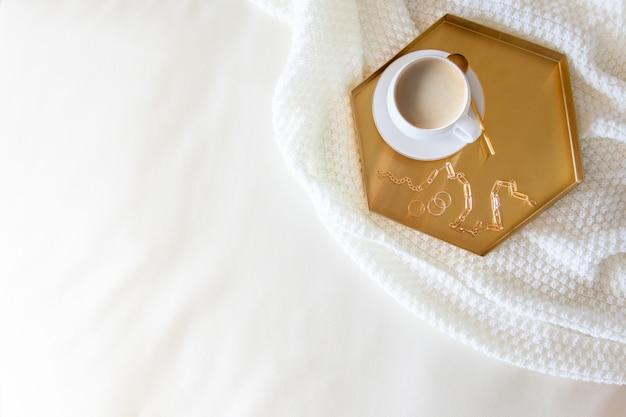 Śniadanie dla kobiety w łóżku. kawa w białym kubku. styl nordycki. biała dzianinowa krata. bukiet kwiatów.