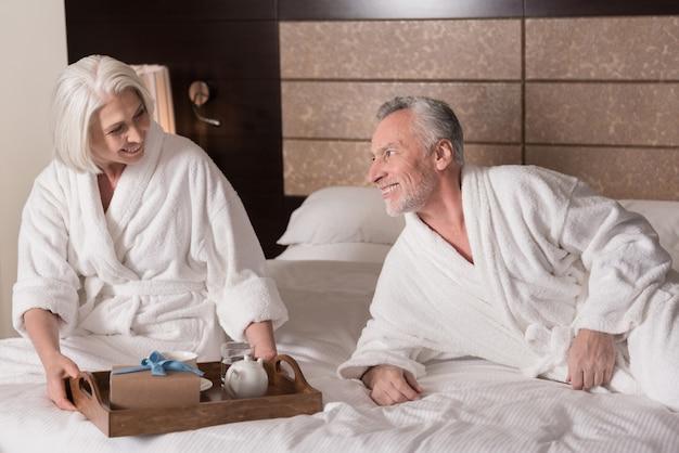 Śniadanie do łóżka. szczęśliwy uśmiechający się para wieku leżąc na łóżku i jedząc śniadanie, wyrażając radość