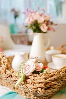 Śniadanie do łóżka, wiklinowa taca z filiżanką kawy z mlekiem, ciastkami i kwiatami