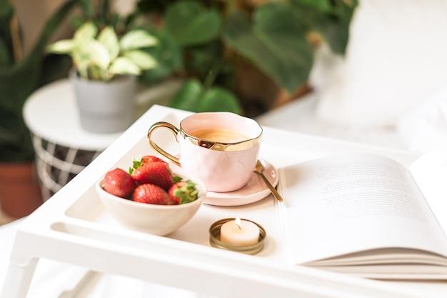 Śniadanie do łóżka z kawą i truskawkami.