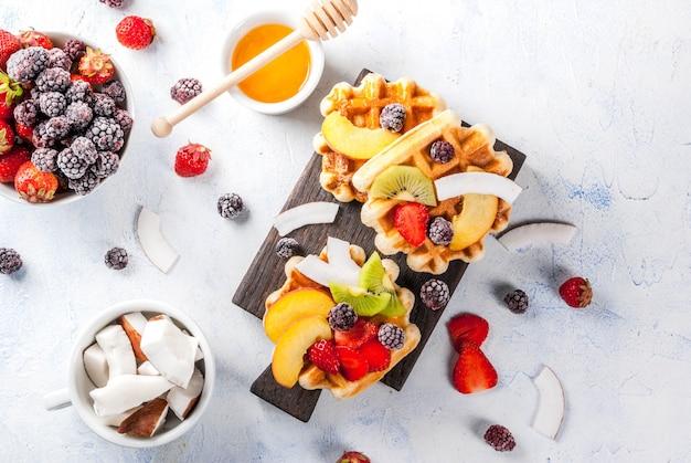 Śniadanie. domowe świeże belgijskie miękkie wafle z miodem, owocami, orzechami, jagodami brzoskwinią, jeżynami, malinami, truskawkami, kokosem, orzechami nerkowca, truskawkami, miętą. lekki stół. widok z góry lato