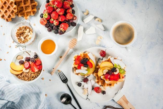 Śniadanie. domowe świeże belgijskie miękkie wafle z miodem, świeżymi owocami, orzechami i jagodami; jogurt z muesli i owocami, filiżanka kawy. lekki betonowy stół. skopiuj widok z góry