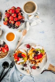 Śniadanie. domowe świeże belgijskie miękkie wafle z miodem, świeżymi owocami, orzechami i jagodami; jogurt z muesli i owocami, filiżanka kawy. lekki betonowy stół. widok z góry