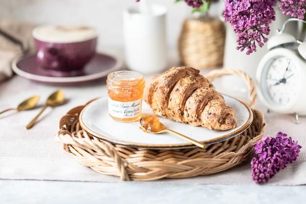 Śniadanie francuski rogalik, dżem, filiżanka kawy, mleko i śmietana i kwiaty bzu. ranek