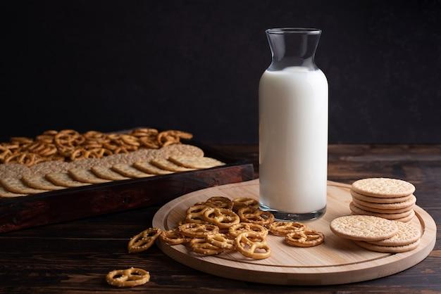 Śniadanie i przekąska butelka mleka z ciasteczkami i mini precle solone na ciemnym tle drewnianych.