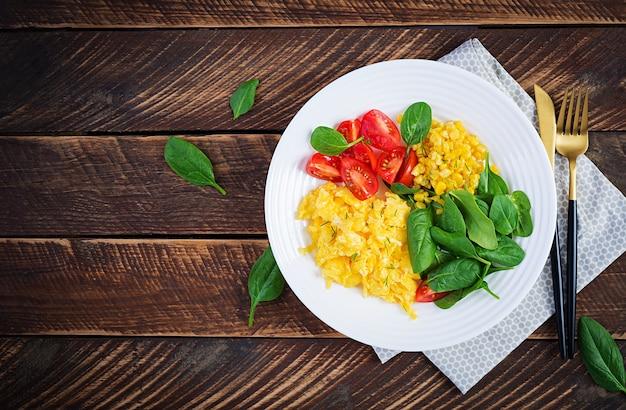 Śniadanie. jajecznica z pomidorkami koktajlowymi, szpinakiem i kukurydzą. widok z góry, układ płaski, powyżej