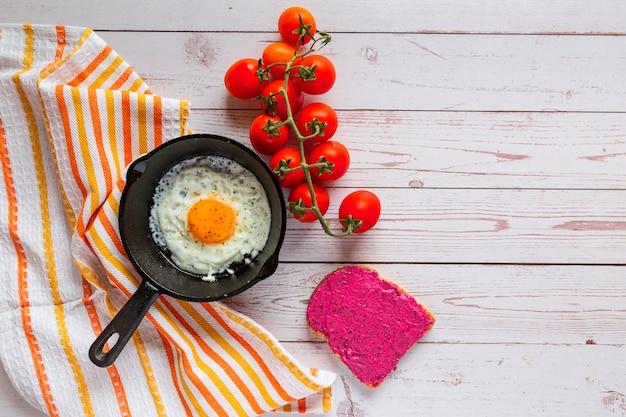 Śniadanie, jajko sadzone na żeliwnej patelni z salaterką, pastą z buraków i świeżymi pomidorkami koktajlowymi