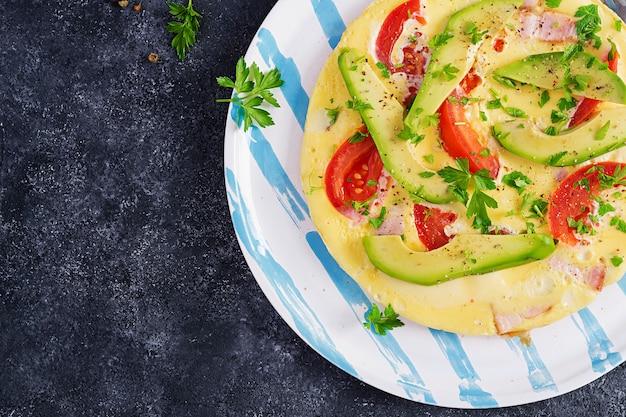 Śniadanie keto. omlet z szynką, pomidorami i awokado na szarym stole. włoski frittata. keto, ketogeniczny obiad. widok z góry, narzut, miejsce na kopię