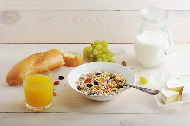 Śniadanie kontynentalne składa się ze zbóż, winogron, soku pomarańczowego, mleka, chleba, bagietki, sera