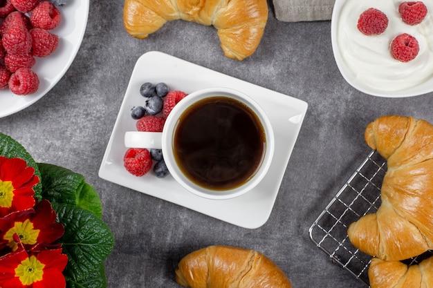 Śniadanie kontynentalne z rogalikami, czarną kawą, śmietaną, malinami i jagodami na ciemnoszarej powierzchni betonowej