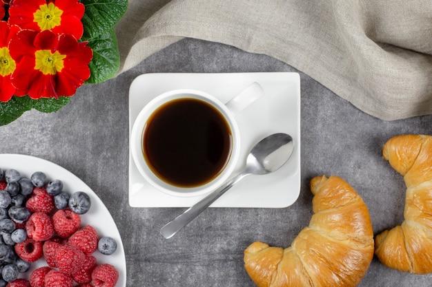 Śniadanie kontynentalne z rogalikami, czarną kawą w białym kubku, malinami, jagodami i kwiatami na szarym betonie.