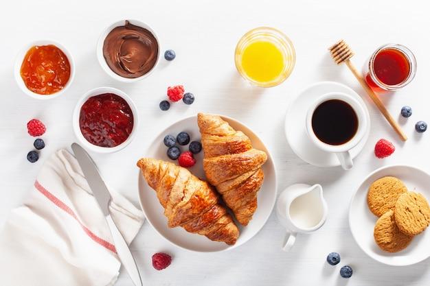 Śniadanie kontynentalne z rogalikiem, dżemem, czekoladą i kawą. widok z góry
