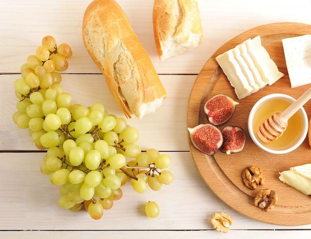 Śniadanie kontynentalne z serem, miodem, figami, orzechami włoskimi, winogronami i bagietką