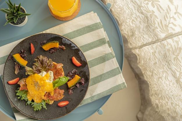 Śniadanie lub brunch, jajka benedykta podawane ze smażonym boczkiem i grzankami udekorowane plastrem truskawki