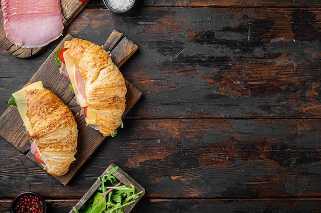 Śniadanie, lunch biznesowy, kanapki zestaw rogalików, ziołami i składnikami, na tle starego ciemnego drewnianego stołu, płaski widok z góry, z miejscem na tekst