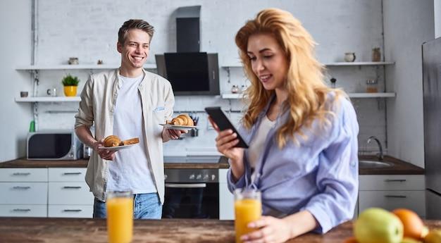 Śniadanie młodej pary zakochanej w domowej kuchni. piękna dziewczyna z telefonem w ręku pije sok. chłopak ugotował śniadanie.