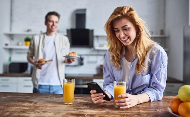 Śniadanie młodej pary zakochanej w domowej kuchni. piękna dziewczyna z telefonem w ręku pije sok.