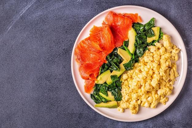 Śniadanie na diecie ketogenicznej, jajecznica, łosoś, awokado, szpinak, widok z góry.