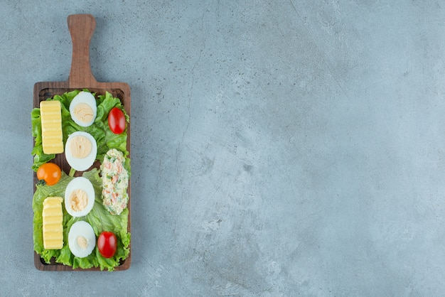 Śniadanie na drewnianej tacy z warzywami, jajkiem na twardo, masłem i porcją sałatki na marmurowym tle. wysokiej jakości zdjęcie