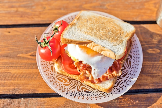 Śniadanie na łonie natury jajka sadzone z tostem smażonym na bekonie i gorącą kawą z termosu