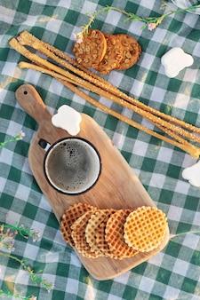 Śniadanie na łonie natury. kubek kawy i ciasteczka na desce na obrusie w kratkę.