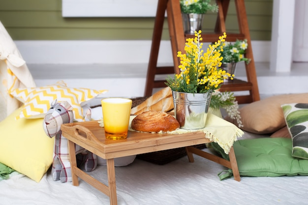 Śniadanie na przytulnej werandzie. domowa lemoniada na werandzie w upalny dzień. letni wiejski dziedziniec z poduszkami, kwiatami mimozy i lemoniadą. piękny letni wieczór na drewnianym tarasie lub patio. drewniana taca