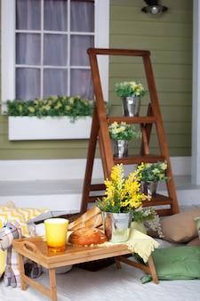 Śniadanie na przytulnej werandzie. domowa lemoniada na werandzie w upalny dzień. letni wiejski dziedziniec z poduszkami, kwiatami mimozy i lemoniadą. piękny letni wieczór na drewnianym tarasie lub patio.