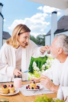 Śniadanie na zewnątrz. kochająca, rozpromieniona para ubrana w białe szlafroki, jedząca śniadanie na letnim tarasie
