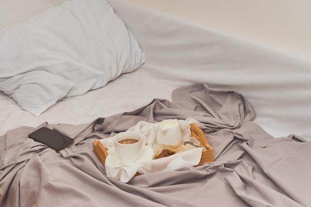 Śniadanie na zmiętym łóżku, kawa, rogaliki, książka, telefon komórkowy