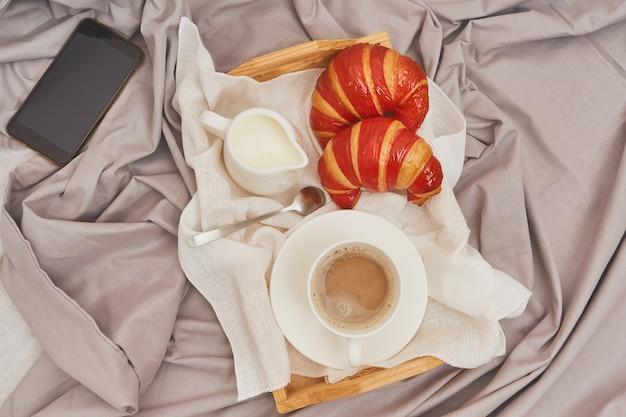 Śniadanie na zmiętym łóżku, kawa, rogaliki, telefon komórkowy