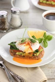 Śniadanie. najlepsze jajka po benedyktyńsku na kromce tostowego chleba zbożowego z guacamole i szpinakiem
