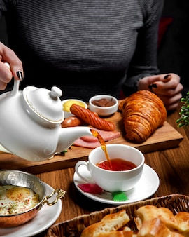 Śniadanie nakryte na stole z czarną herbatą