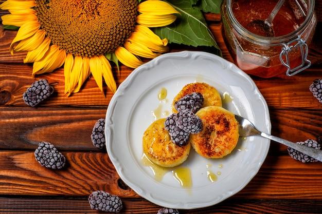 Śniadanie. naleśniki z twarogu z miodem ozdobione jagodami i słonecznikami na drewnianym stole