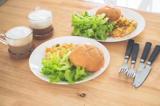 Śniadanie omlet sałatka burger serwowana z kawą.