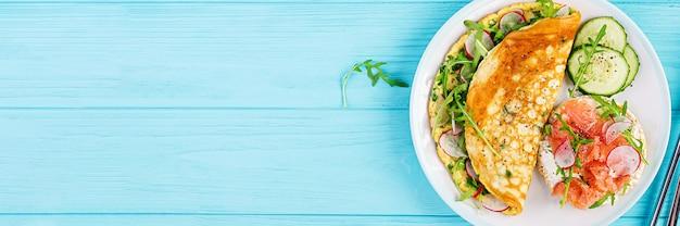 Śniadanie. omlet z rzodkiewką, zieloną rukolą i kanapką z łososiem na białym talerzu. frittata - omlet włoski. widok z góry