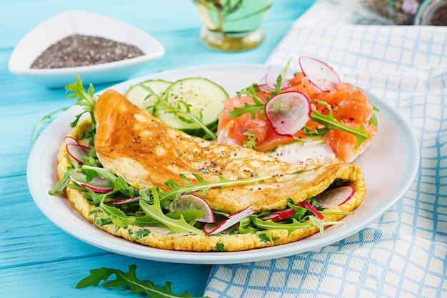 Śniadanie. omlet z rzodkiewką, zieloną rukolą i kanapką z łososiem na białym talerzu