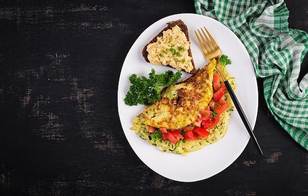 Śniadanie. omlet z sałatką z cukinii, sera i pomidorów z kanapką na białym talerzu. frittata - włoski omlet. widok z góry, układ płaski