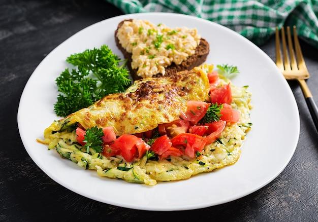 Śniadanie. omlet z sałatką z cukinii, sera i pomidorów z kanapką na białym talerzu. frittata - włoski omlet.