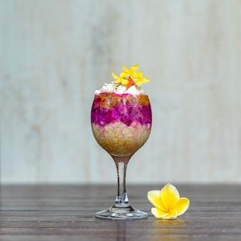 Śniadanie owocowe w szklance płatków owsianych, owoc czerwonego smoka, marakuja, mango i miód w białym drewnianym drewnie