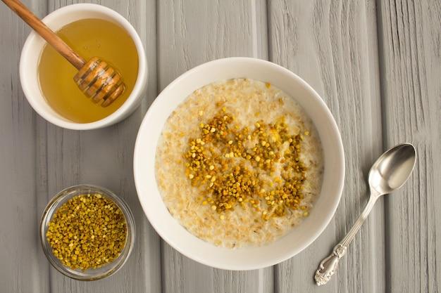 Śniadanie: płatki owsiane z pyłkiem pszczelim i miodem w białej misce na szarym tle drewnianych. widok z góry.