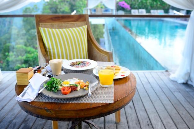 Śniadanie podawane ze smażonym jajkiem, kawą, sokiem pomarańczowym, płatkami i owocami dla zdrowia.