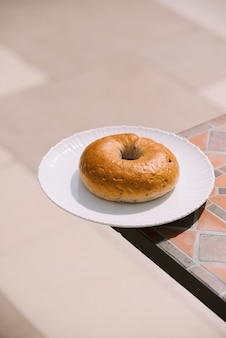 Śniadanie rano słoneczna ciepła pogoda z pączka na białej płytce na tle tabeli. dobry nastrój widok poziomy