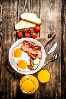 Śniadanie rano. smażony boczek z jajkiem i sokiem pomarańczowym. na drewnianym stole.