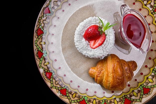 Śniadanie. rogalik z twarogiem, truskawkami i dżemem, na talerzu koloru, na czarnym tle. widok z góry