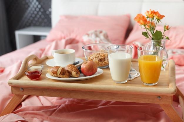 Śniadanie serwowane w łóżku na drewnianej tacy z kawą i rogalikami