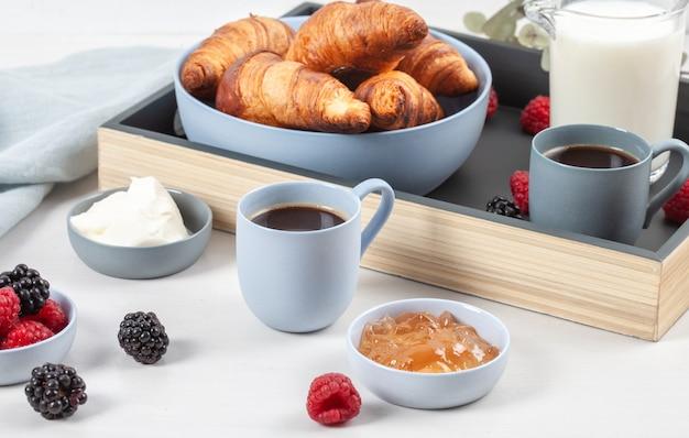 Śniadanie serwowane z kawą, rogalikami, świeżymi jagodami, mlekiem, śmietaną, dżemem