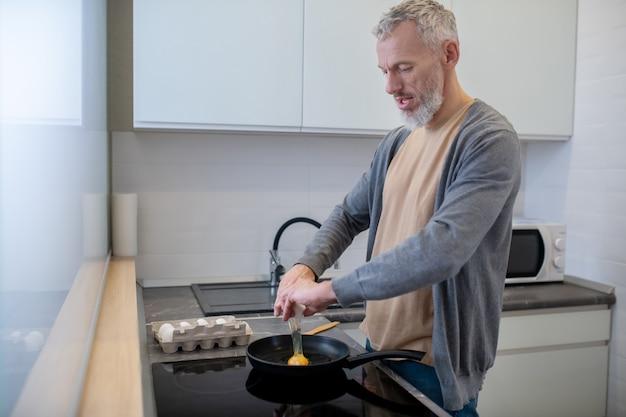 Śniadanie. siwowłosy mężczyzna gotuje omlet w kuchni