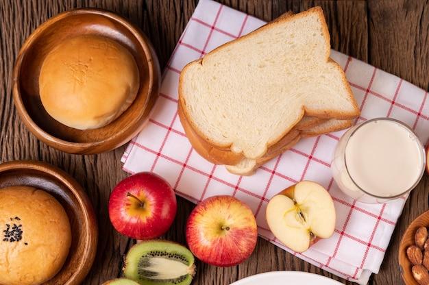 Śniadanie składa się z chleba, jabłek, winogron i kiwi na drewnianym stole